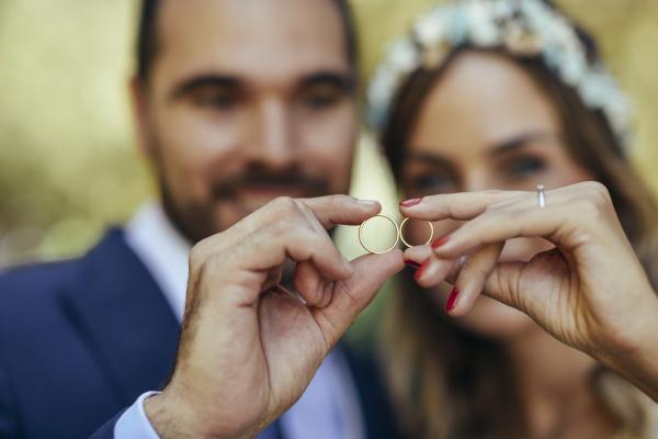 feliz pareja nupcial mostrando sus anillos