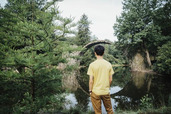 adolescente mirando el tranquilo puente de