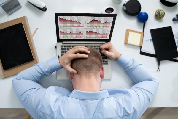 empresario estresado frente a una computadora
