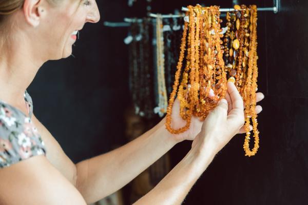 mujer mirando un collar hecho de
