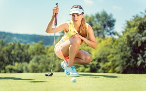 mujer en campo de golf tomando