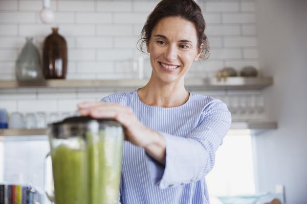 mujer sonriente haciendo batido verde saludable