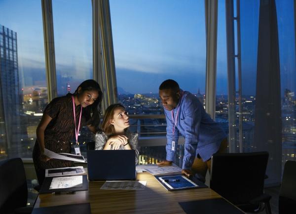 empresarios trabajando hasta tarde en portatil