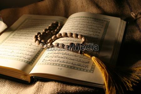 libro sagrado del coran con rosario