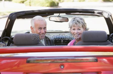 pareja en coche convertible sonriendo