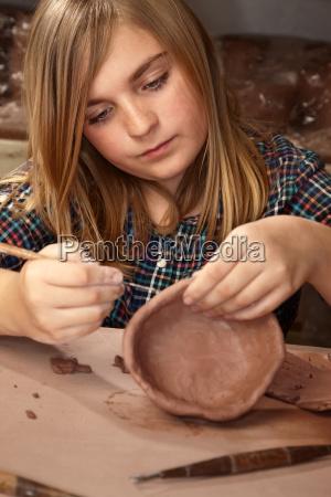 joven chica haciendo tazon en estudio
