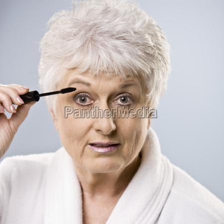 mujer mayor poniendose maquillaje