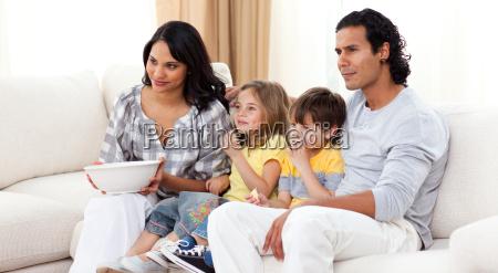 familia sonriente viendo tv en el