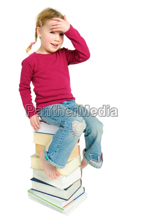 child on a pile of books