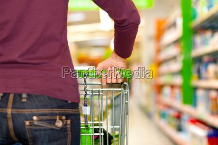 mujer en supermercado con carrito de
