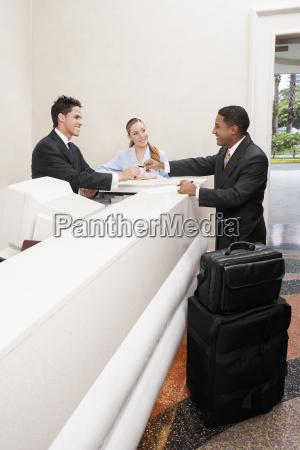 hombre de negocios y dos recepcionistas
