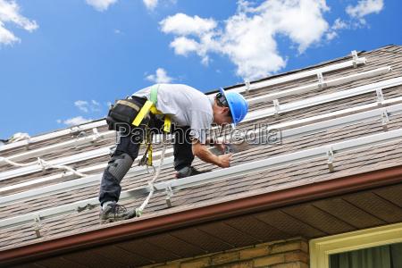 hombre trabajando en el tejado instalando