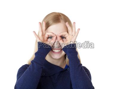joven atractiva mujer hace binoculares con