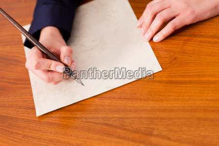 mujer escribe una carta con pluma