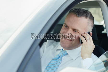 businessman in car talking on mobile
