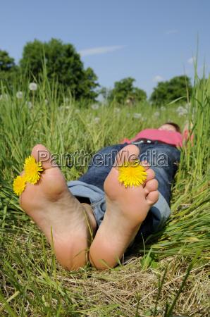la mujer joven yace descalza sobre