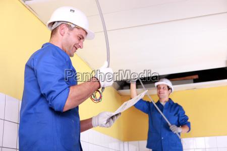 dos electricistas en una habitacion en