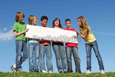 grupo de diversos ninyos con cartel