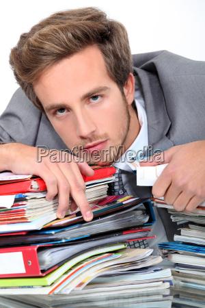 joven acostado en un escritorio lleno