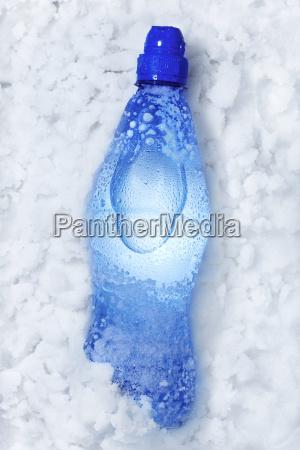 botella de refresco en la nieve