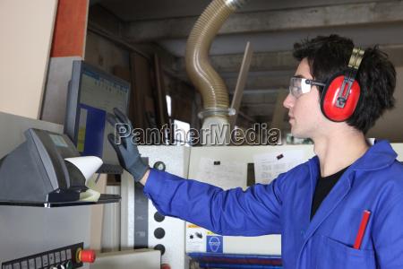 hombre joven operando maquinaria de fabrica