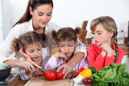 madre y sus hijas haciendo ensalada
