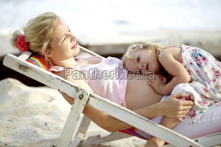 joven madre embarazada sentada con su