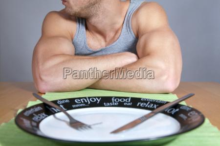 hombre muscular con el plato vacio