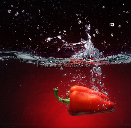 pimienta roja cayendo en el agua