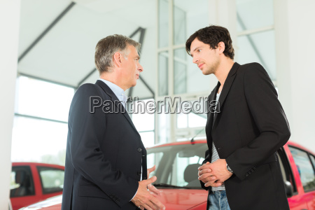 senior and young man with cars