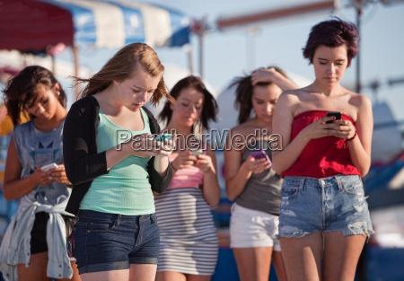 senyoras jovenes usando sus telefonos