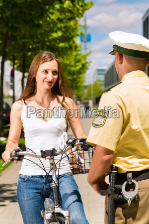 woman on bicycle with police in