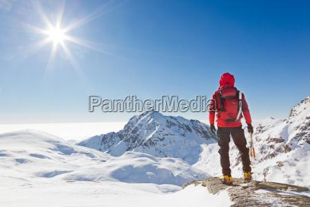montanyero mirando un paisaje nevado de