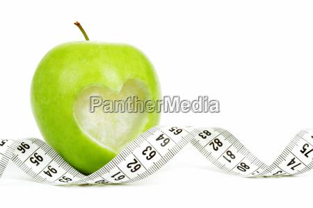 manzana verde con cinta metrica y