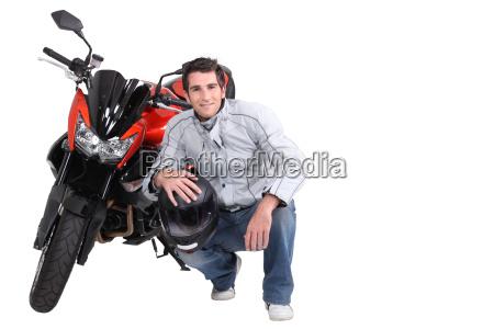 hombre agachado junto a la motocicleta