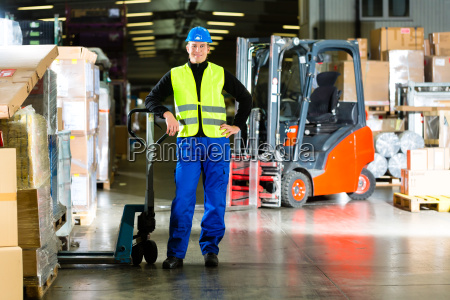 warehouse operator with pallet truck in