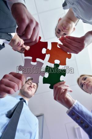 grupo de empresarios que montan rompecabezas
