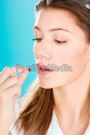 mujer tomando pastilla roja
