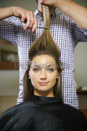woman in hairdresser shop cutting long