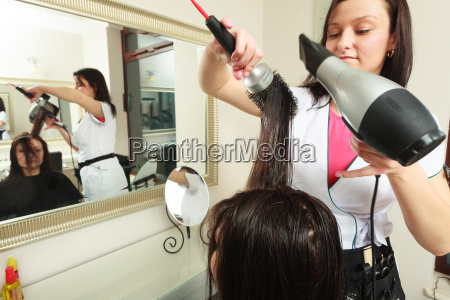 hairstylist drying hair woman client in
