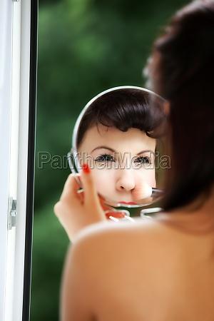 girl applying make up reflection in