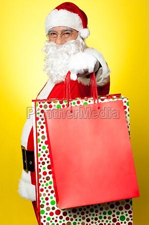 cheerful santa holding vibrant colored shopping
