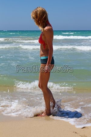 young woman walking on the sand