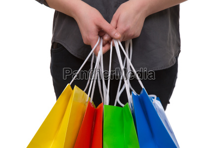 a woman holds colorful shopping bags