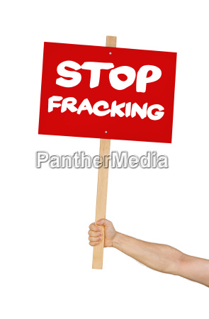 person holds sign reading stop fracking