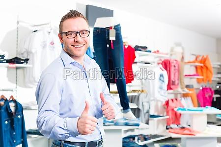 hombre apuesto comprar los pantalones vaqueros