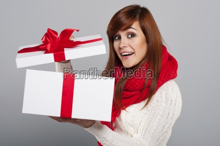 happy young woman opening christmas gift