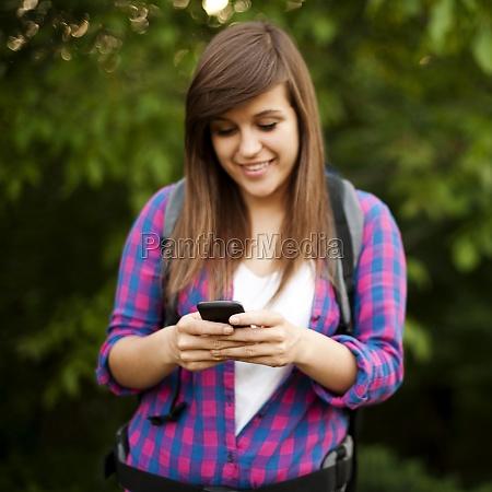 beautiful female hiker texting