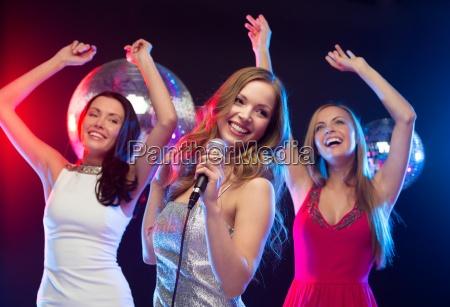 tres mujeres sonrientes bailando y cantando