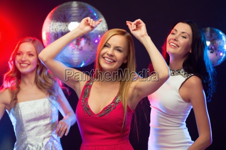 tres mujeres sonrientes bailando en el